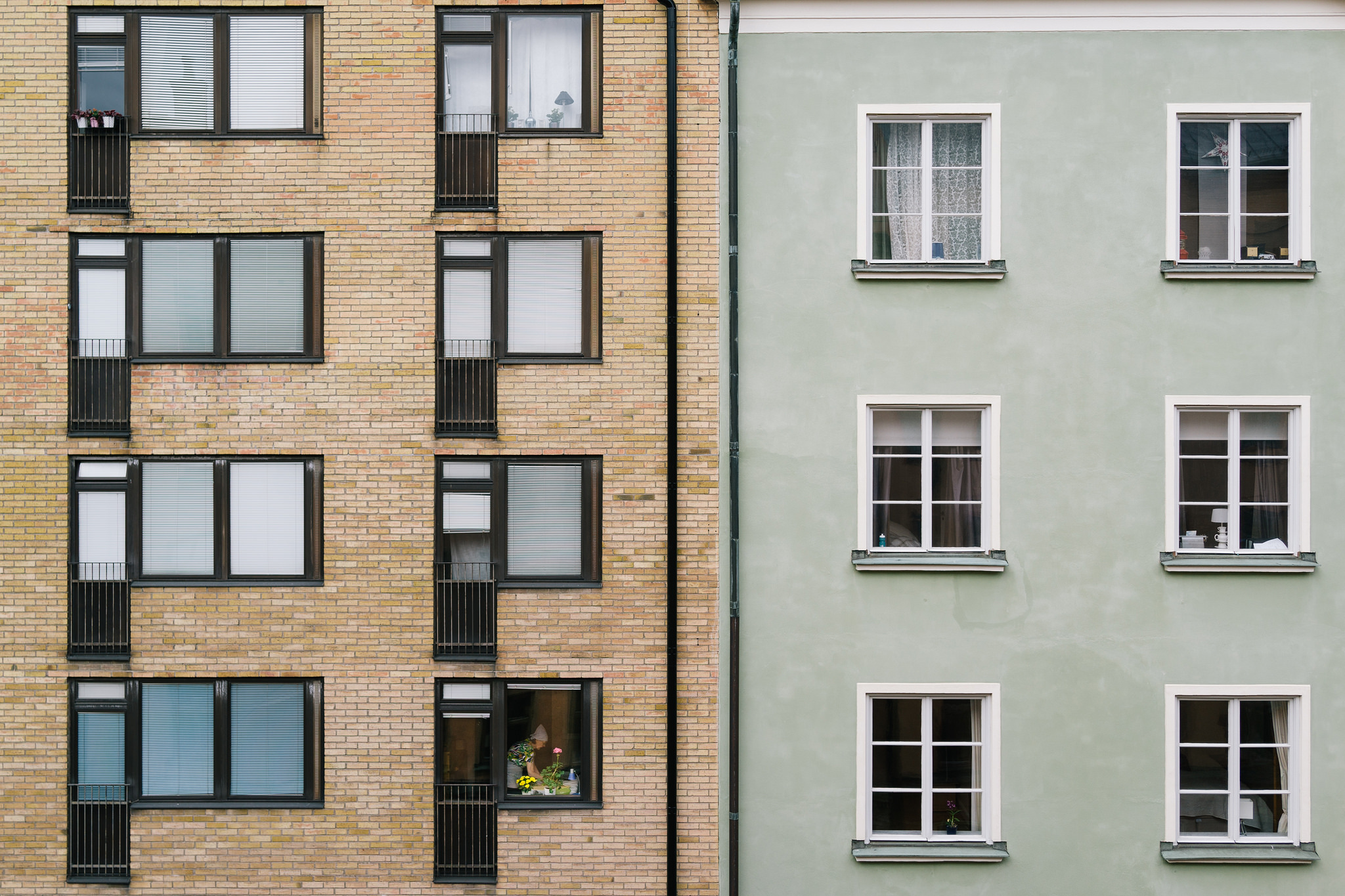 Hyreshus med bakande kvinna i fönster